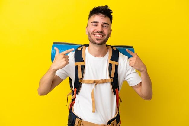 Молодой кавказский альпинист с большим рюкзаком, изолированным на желтом фоне, жестом показывает палец вверх
