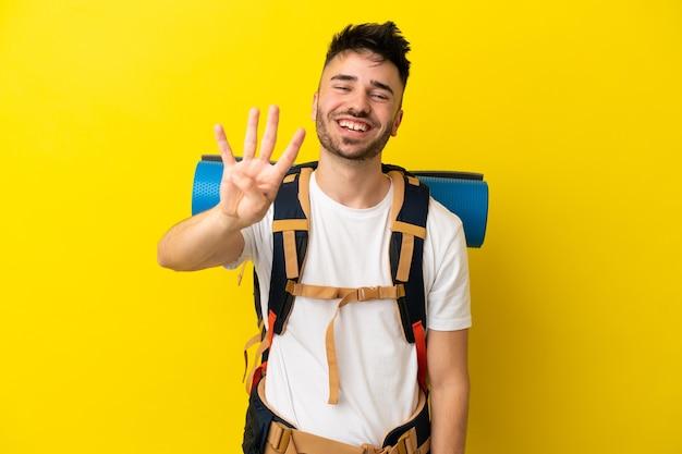 Молодой кавказский альпинист с большим рюкзаком на желтом фоне счастлив и считает четыре пальцами