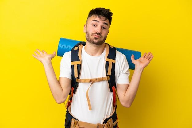 Молодой кавказский альпинист с большим рюкзаком, изолированным на желтом фоне, сомневается, поднимая руки