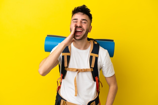Молодой кавказский альпинист с большим рюкзаком, изолированным на желтом фоне, кричит с широко открытым ртом