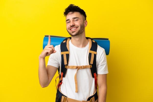 Молодой кавказский альпинист с большим рюкзаком на желтом фоне показывает и поднимает палец в знак лучших