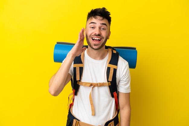Молодой кавказский альпинист с большим рюкзаком изолирован на желтом фоне с удивлением и шокированным выражением лица