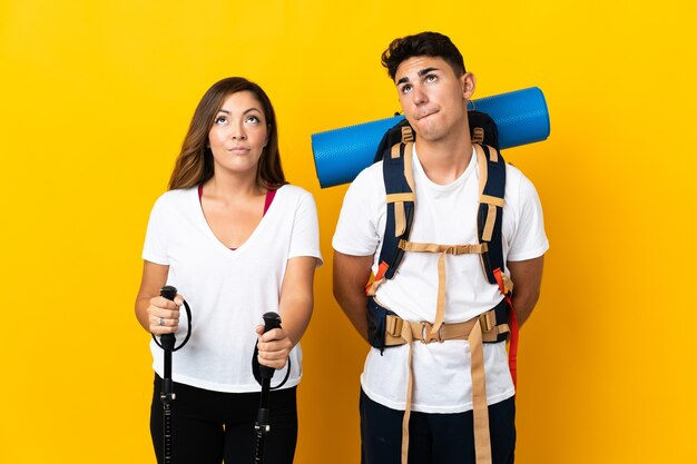 黄色の大きなバックパックと見上げる若い登山家のカップル
