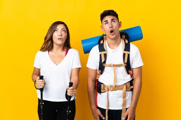 見上げる黄色の大きなバックパックと驚きの表情を持つ若い登山家のカップル