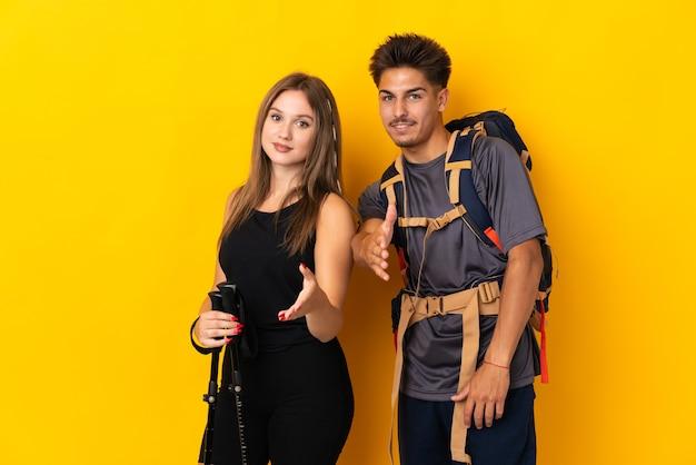 좋은 거래를 닫기 위해 악수하는 노란색에 큰 배낭 젊은 등산가 부부