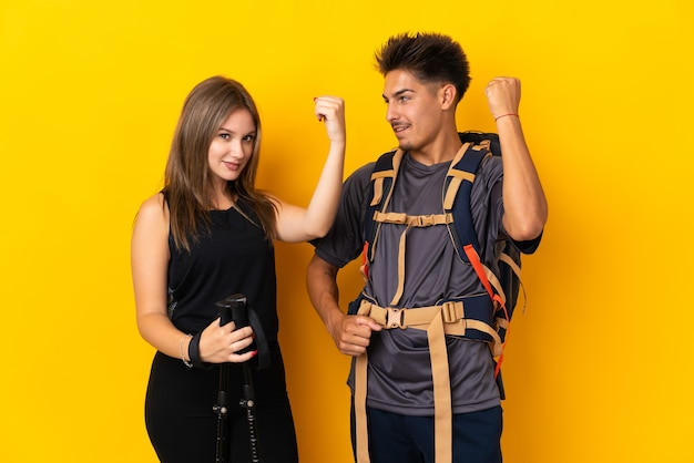 Young mountaineer couple with a big backpack on yellow celebrating a victory in winner position