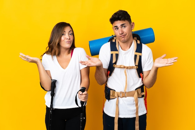 Young mountaineer couple with a big backpack on yellow having doubts while raising hands
