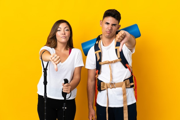 Young mountaineer couple with a big backpack on yellow showing thumb down with negative expression
