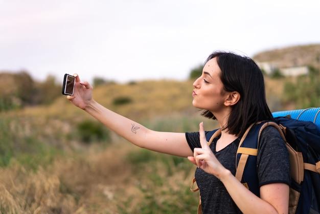 Молодая альпинистка делает селфи с мобильным телефоном с большим рюкзаком на открытом воздухе