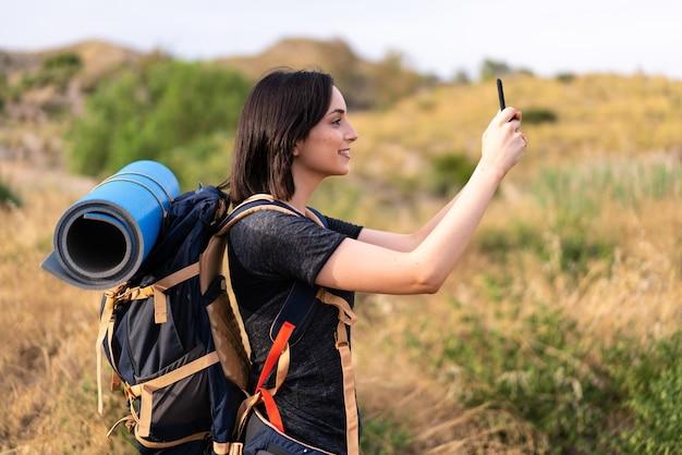 屋外で大きなバックパックを持って携帯電話で自分撮りをしている若い登山家の女の子