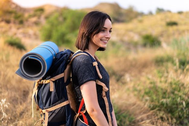 屋外で大きなバックパックを持つ若い登山家の女の子