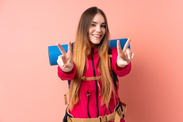 笑みを浮かべて勝利のサインを示すピンクの壁に分離された大きなバックパックを持つ若い登山少女