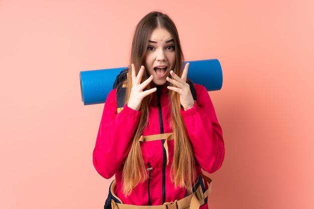 Молодая девушка альпиниста с большим рюкзаком на розовой стене с удивленным выражением лица