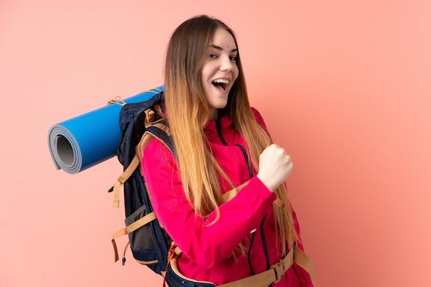 勝利を祝っているピンクの壁に大きなバックパックを持つ若い登山家少女