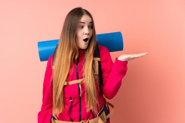 Молодая девушка альпиниста с большим рюкзаком на розовой стене держит воображаемое пустое пространство на ладони