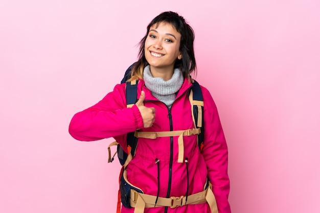 親指のジェスチャーを与える孤立したピンクの上の大きなバックパックを持つ若い登山家少女