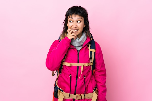 Молодая альпинистка с большим рюкзаком над изолированным розовым нервной и напуганной