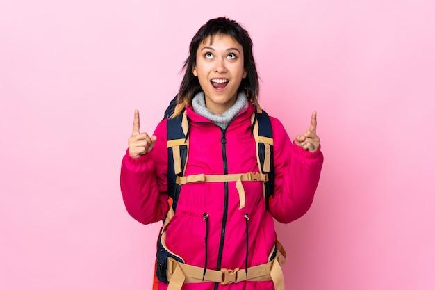 人差し指で素晴らしい分離を指している孤立したピンクの上の大きなバックパックを持つ若い登山家少女素晴らしいアイデア