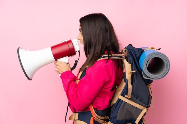 확성기를 통해 외치는 고립 된 분홍색 위에 큰 배낭을 가진 젊은 산악인 소녀