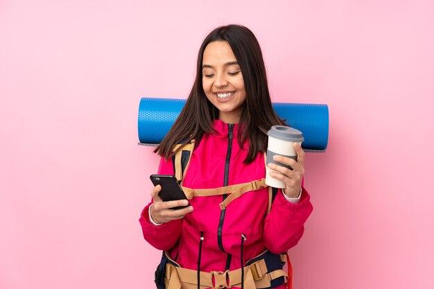 持ち帰り用のコーヒーと携帯電話を保持している孤立したピンクの壁の上に大きなバックパックを持つ若い登山家の女の子