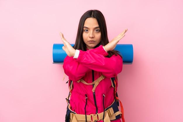 Молодая альпинистка с большим рюкзаком на изолированной розовой стене не делает жест