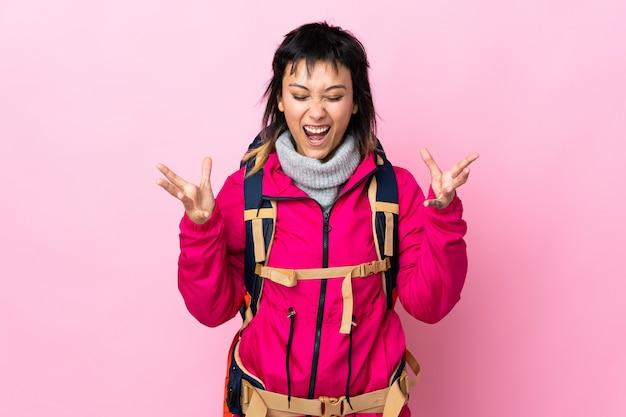 Молодая альпинистка с большим рюкзаком над изолированной розовой стеной несчастна и разочарована чем-то
