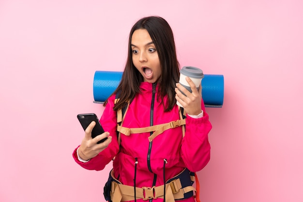 持ち帰り用のコーヒーと携帯電話を保持しているピンクの上の大きなバックパックを持つ若い登山家の女の子