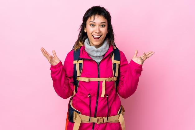 Молодая альпинистка с большим рюкзаком на розовой стене с удивленным выражением лица