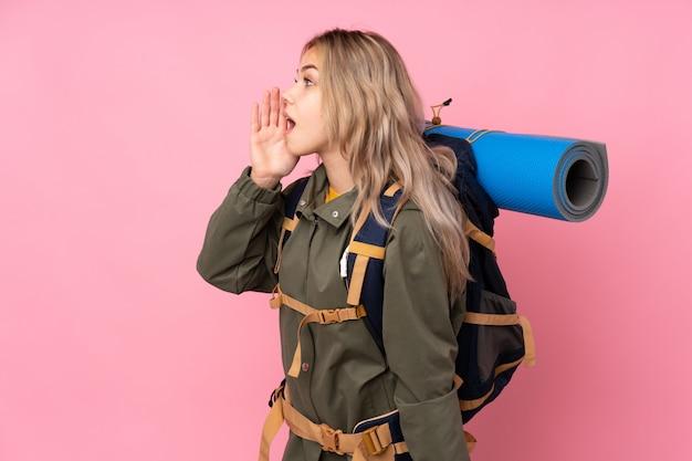 Молодая альпинистка с большим рюкзаком над стеной