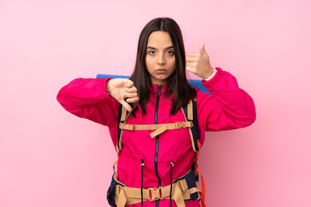 Young mountaineer girl with a big backpack over isolated pink background making good-bad sign. undecided between yes or not