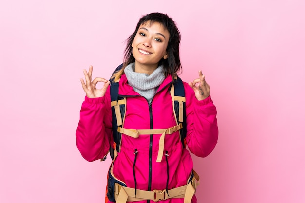 Young mountaineer girl with a big backpack over isolated pink showing an ok sign with fingers