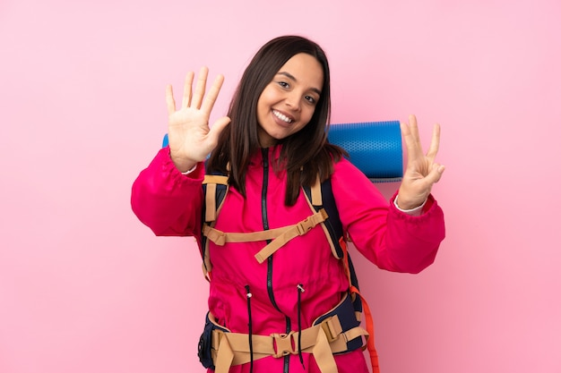 Young mountaineer girl with a big backpack over isolated pink wall counting eight with fingers