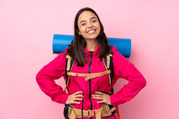 Young mountaineer girl with a big backpack over isolated pink wall posing with arms at hip and smiling