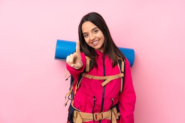 Young mountaineer girl with a big backpack over isolated pink wall showing and lifting a finger