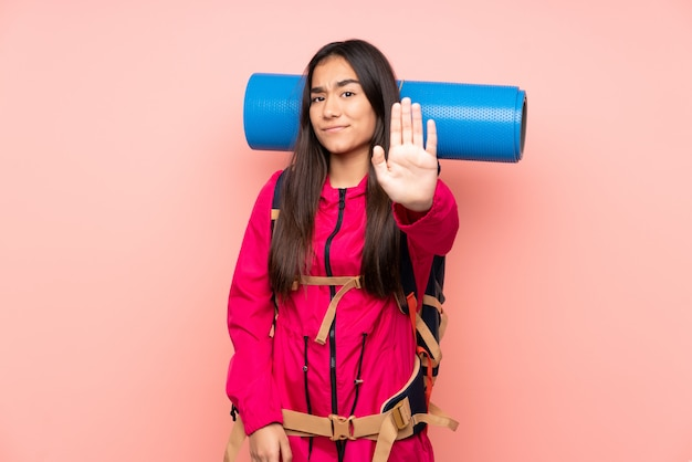 Young mountaineer girl with a big backpack on pink making stop gesture with her hand