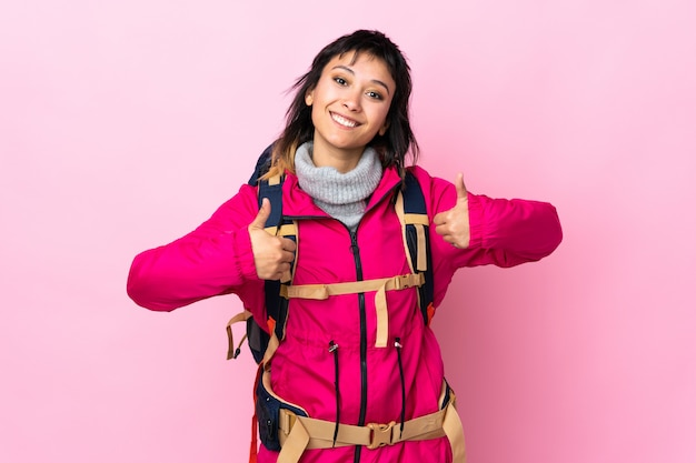 Young mountaineer girl with a big backpack over pink wall giving a thumbs up gesture