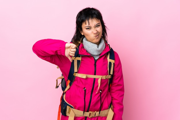 Young mountaineer girl with a big backpack over pink wall showing thumb down sign