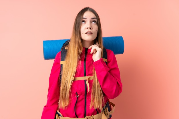 Young mountaineer girl with a big backpack on pink wall thinking an idea