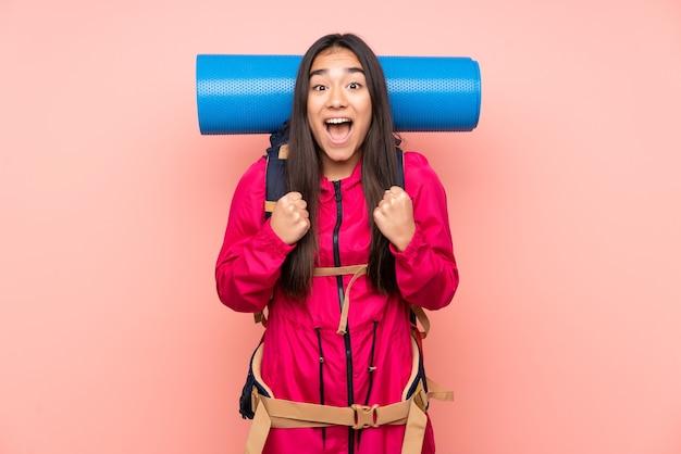 Молодая индийская девушка-альпинист с большим рюкзаком, изолированным на розовом, празднует победу