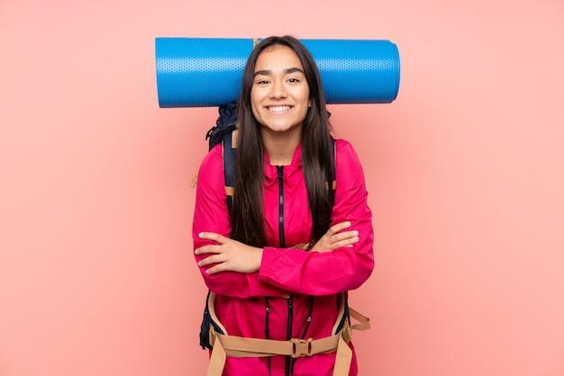 Индийская девушка молодой альпинист с большим рюкзаком изолирована на розовом смеясь