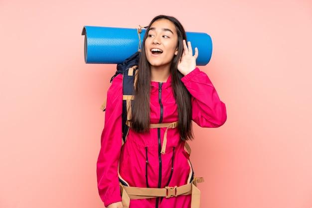 Индийская девушка молодой альпинист с большим рюкзаком изолирована на розовом, слушая что-то