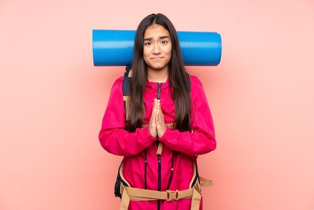 Индийская девушка молодой альпинист с большим рюкзаком изолирована на розовой мольбе