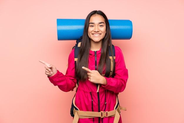 Индийская девушка молодой альпинист с большим рюкзаком изолирована на розовом указывая пальцем в сторону