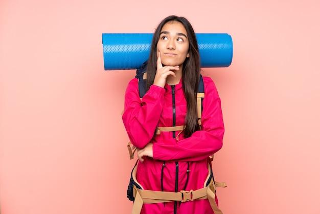 Молодая индийская девушка-альпинист с большим рюкзаком изолирована на розовом, думая об идее