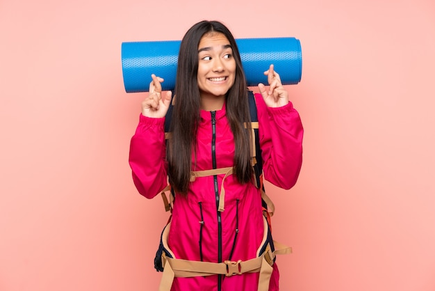 Young mountaineer indian girl with a big backpack isolated on pink wall with fingers crossing