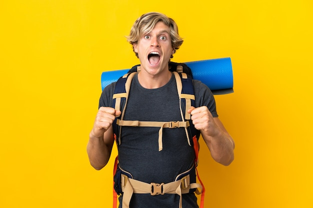 Young mountaineer man over isolated yellow background celebrating a victory in winner position