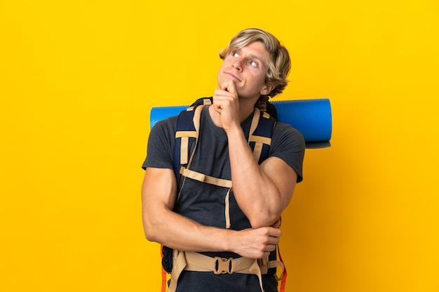 Молодой альпинист на изолированном желтом фоне и смотрит вверх