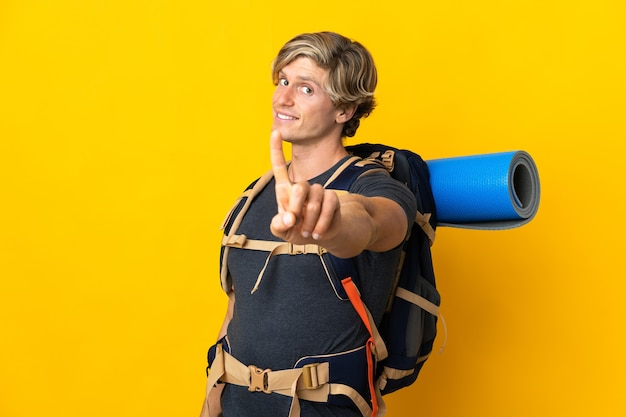 指を見せて持ち上げる孤立した黄色の上の若い登山家の男
