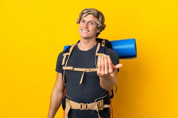 손으로와 서 초대 격리 된 노란색 벽에 젊은 산악인 남자. 와줘서 행복해
