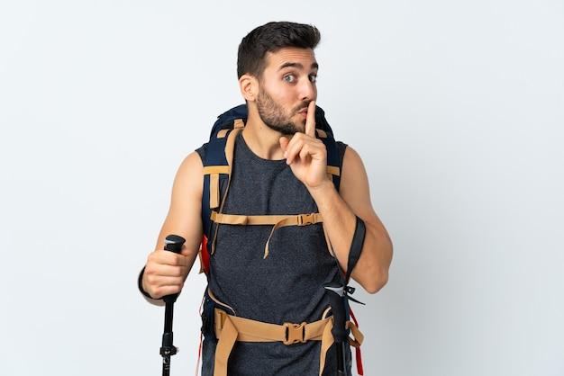 沈黙のジェスチャーをしている白で隔離の大きなバックパックとトレッキングポールを持つ若い登山家の男